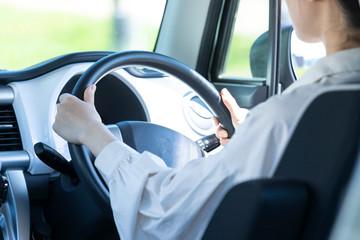 車のハンドルを握る若い女性の手元