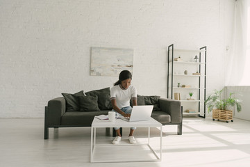 young african american freelancer working on laptop in spacious living room
