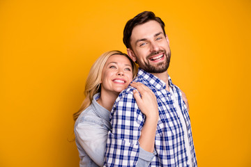 Photo beautiful wife lady handsome husband guy couple hug his strong back feel safety good mood in love perfect pair hold arms wear casual shirts clothes isolated yellow color background