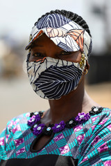 Nigerian fashion stylist, Angela Innocent, 38, poses for a picture with a fabric face mask matching her hat, following the spread of the coronavirus disease (COVID-19) in Lagos