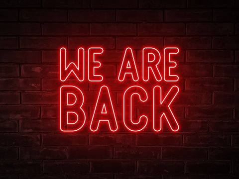 We are back - red neon light word on brick wall background