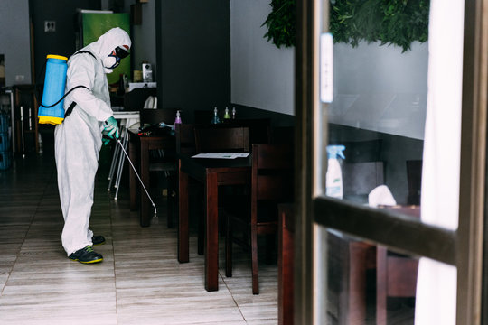 Worker in hazmat suit wearing face mask protection while making disinfection inside bar restaurant - Coronavirus decontamination for people healthcare - Focus on man's head