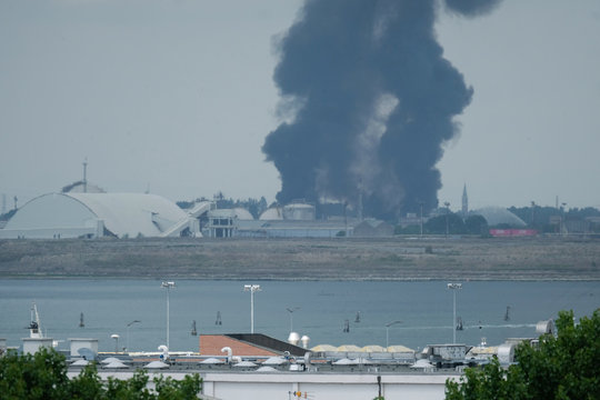 Large clouds of black smoke billows from a chemical plant after an explosion, in Marghera, seen from Venice