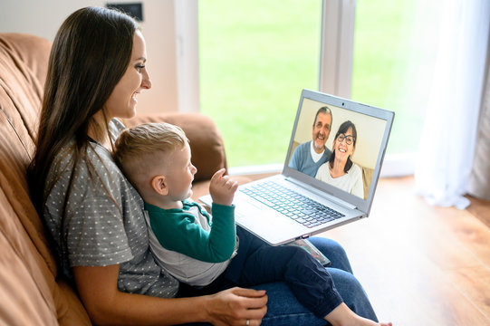 Little grandson is talking via video call on laptop with a grandparents. A young mother with a baby son sit on a sofa at home and have a video meeting grandparent are on a laptop screen