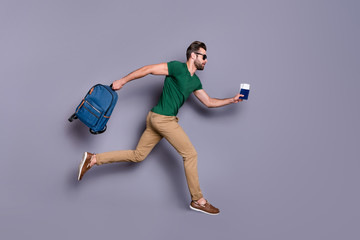 Full body profile side photo of serious guy jump run dont want miss check in passing board hold visa tickets bag backpack wear green trousers isolated over gray color background