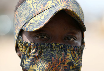 A woman poses for a picture with a fabric protective face mask on, matching with her hat, following the spread of the coronavirus disease (COVID-19) in Lagos