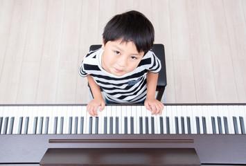 ピアノの練習をする小学生の男の子