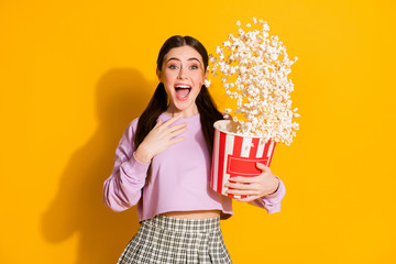 Portrait of amazed enthusiastic girl watch incredible funky series hold big box pop corn flying wear jumper checkered isolated over bright shine color background