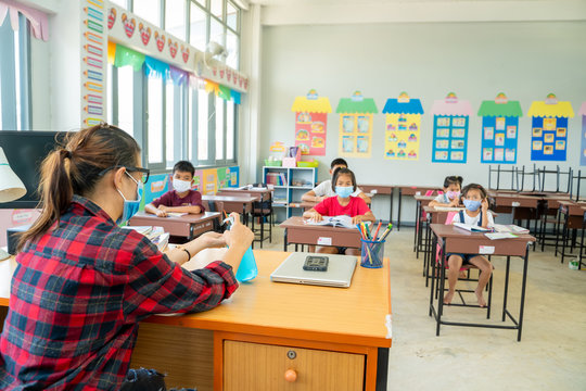 Teacher wearing protective mask to Protect Against Covid-19,Group of school kids with teacher sitting in classroom online and raising hands,Elementary school,Learning and people concept.