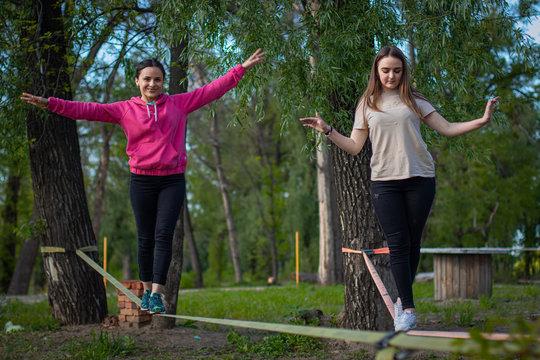 two teenage girl balancing on slackline with sky view