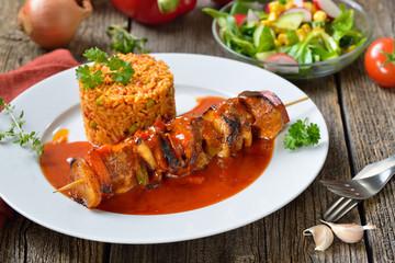 Deftiger Schaschlik-Spieß in pikanter Sauce mit Djuvec-Reis und gemischtem Beilagensalat serviert  – Hearty shashlik skewer in a spicy sauce with Djuvec rice and mixed side salad