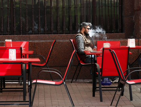 A man smokes a hookah as he rests at the terrace of a cafe in Kiev