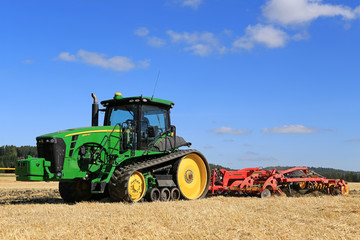 John Deere 8345RT Tracked Tractor and Vaderstad Cultivator on Field. Illustrative Editorial Content.