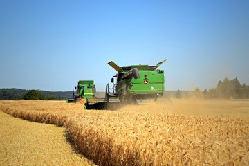 Two John Deere Modern Combines Harvest Barley. Illustrative Editorial Content.