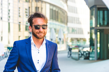 Junger Mann im Anzug mit Sonnenbrille vor Bürogebäude