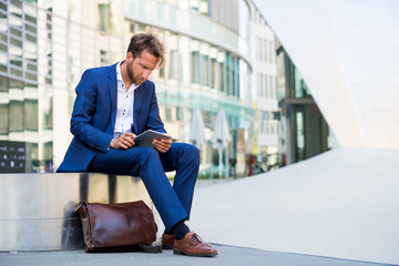 Junger Mann mit Tablett vor Bürogebäude