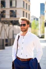 Junger Mann im Anzug schaut in die Sonne