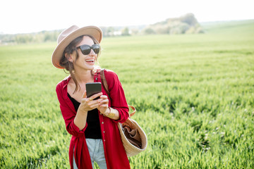 Happy stylish woman using smart phone outdoors, communicating on mobile device while standing on the greenfield