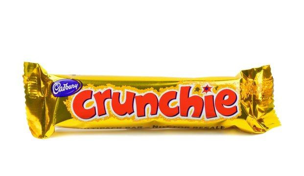 NIEDERSACHSEN, GERMANY FEBRUARY 17.02.2015: A single Cadbury crunchie chocolate bar sealed on a white background