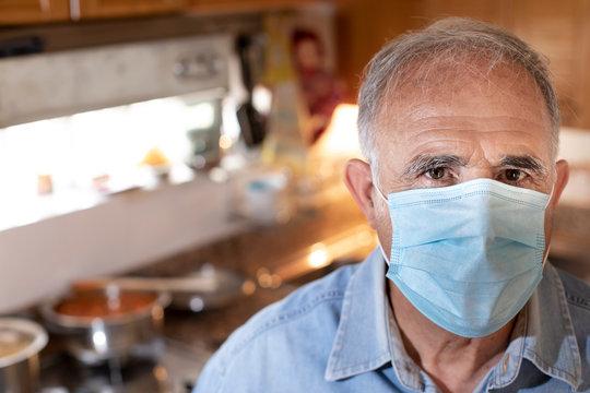 Ritratto di uomo anziano con mascherina protettiva e camicia in jeans da dentro la sua cucina