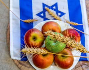 Apples and ears of wheat on plate and background with Israeli flag. All things are symbols for Shavuot - traditional Jewish holiday of Harvest, selective focus on upper ear, still life with apples