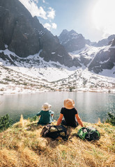 Fototapeta Father and son backpackers resting near the mountain lake Zelene Pleso in Slovakia and enjoying snowy peaks. Spring-summer hiking with kids concept image.