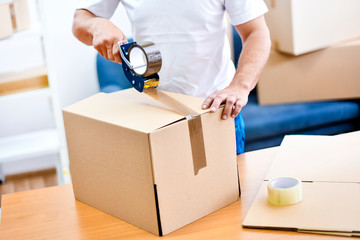Worker hands holding packing machine and sealing cardboard or paper boxes