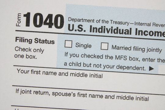 A printed IRS 1040 tax form is shown in 2020 in a macro view. The Internal Revenue Service tax filing deadline has been extended in this year from April 15 to July 15.