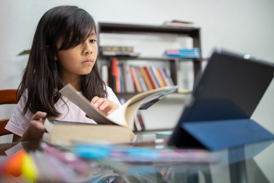 Mexican girl studying online with tablet at home concentrated looking for page in book