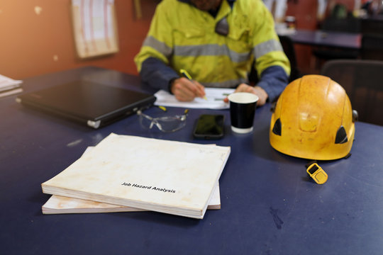 Defocused of miner setting on the chair written Job hazard analysis (JSA) with JSA templates forms on the table construction mine site Perth, Australia