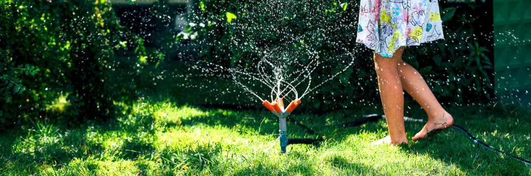 Child playing with garden sprinkler. Happy Girl in dress running and jumping. Kids gardening. Summer outdoor water fun. Children play with gardening hose watering flowers.