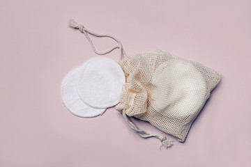 Reusable Bamboo Cotton Makeup Remover Pads in net bag on pink background. Zero-waste, sustainable...