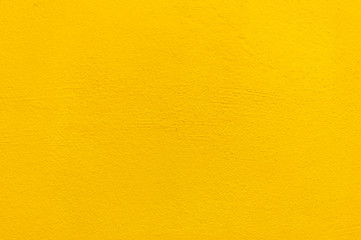 Blurred Yellow stucco wall background. Yellow painted cement wall texture.