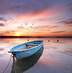 Wall Mural - blaues Holzboot zum Sonnenaufgang