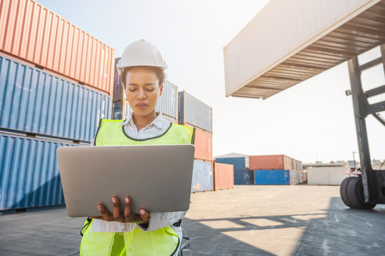Black foreman woman worker working checking at Container cargo harbor holding laptop computer to loading containers. African dock female staff business Logistics import export shipping concept.