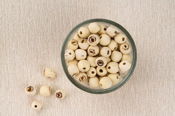 Fototapete - Top view of dried lotus seeds in glass bowl on a table mat. Nowadays lotus seed become popular healthy food and has highly beneficial for health.