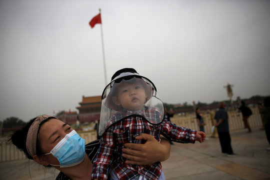 Woman holds a child who wears a protective face cover as they pose for pictures near a Chinese national flag at the Tiananmen Square in Beijing