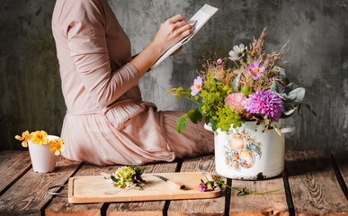female artist draws a composition of wild flowers in a pot in a rustic style, a sketchbook on a table with pencils.