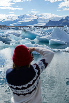 Young girl, female photographer taking a photo of floating ice in Jokulsarlon glacier lagoon in Iceland. Popular tourist destination
