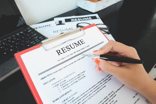 Closeup of resume with pen. computer laptop and glasses on the wooder table