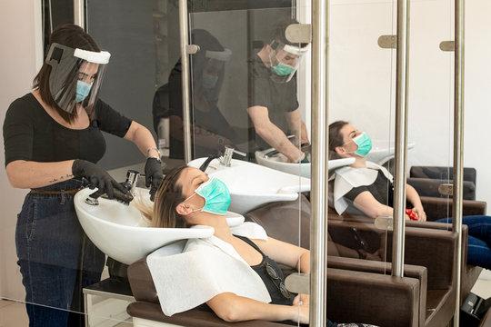 Servizio di lavaggio capelli dentro un salone da parrucchieri con tutte le disposizioni di protezione quali mascherine facciali,