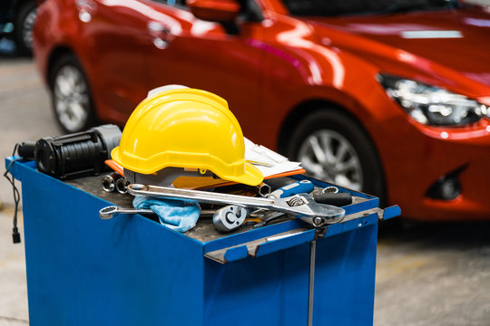 Close-up image of blue metal tool cabinet with safety helmets, glove, document pad on the cabinet with garage background. Automobile repair service.