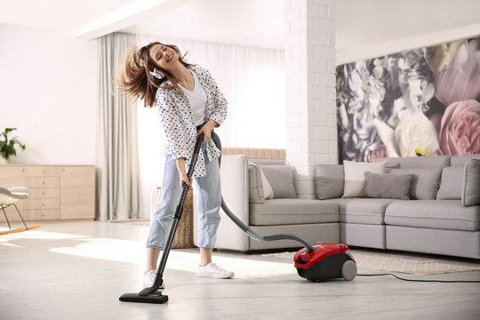 Young woman having fun while vacuuming at home