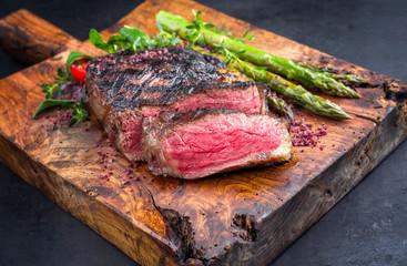 Gegrilltes dry aged Wagyu Entrecote Steak vom Rind mit Tomaten und grünen Spargel als closeup auf...