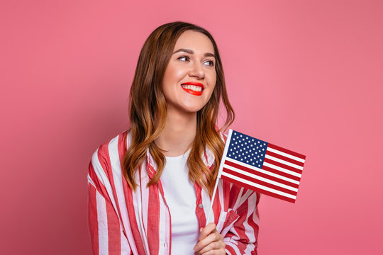 Happy young woman in a red shirt with red lipstick holds a small american flag and smiles isolated over pink background, girl holding USA flag, 4th of july independence day, copy space