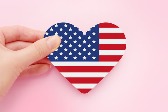 Female hand holds american heart shaped paper flag isolated over pink background, 4th of july independence day of America, celebration, postcard, greeting card