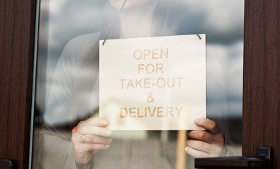 Woman holds the wooden sign with text: Open for take-out and delivery