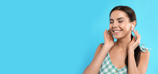 Young woman listening to music with wireless earphones on turquoise background, space for text....
