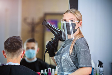 A hairdresser with security measures for Covid-19 holding a hairdryer and looking at the camera in...