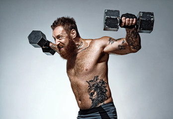 Strong man exercising with dumbbells. Photo of man with naked torso on grey background. Strength and motivation
